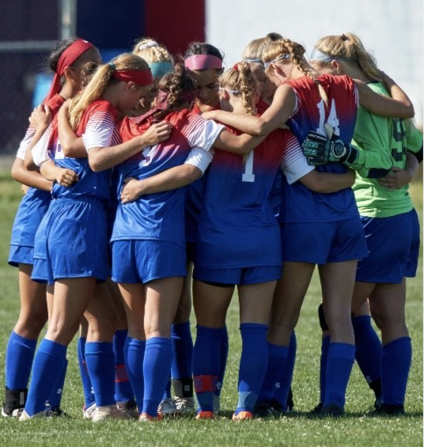 Members of the Varsity girls soccer team huddling together.