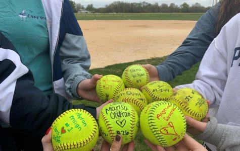 The team signs softballs commemorating their camaraderie.