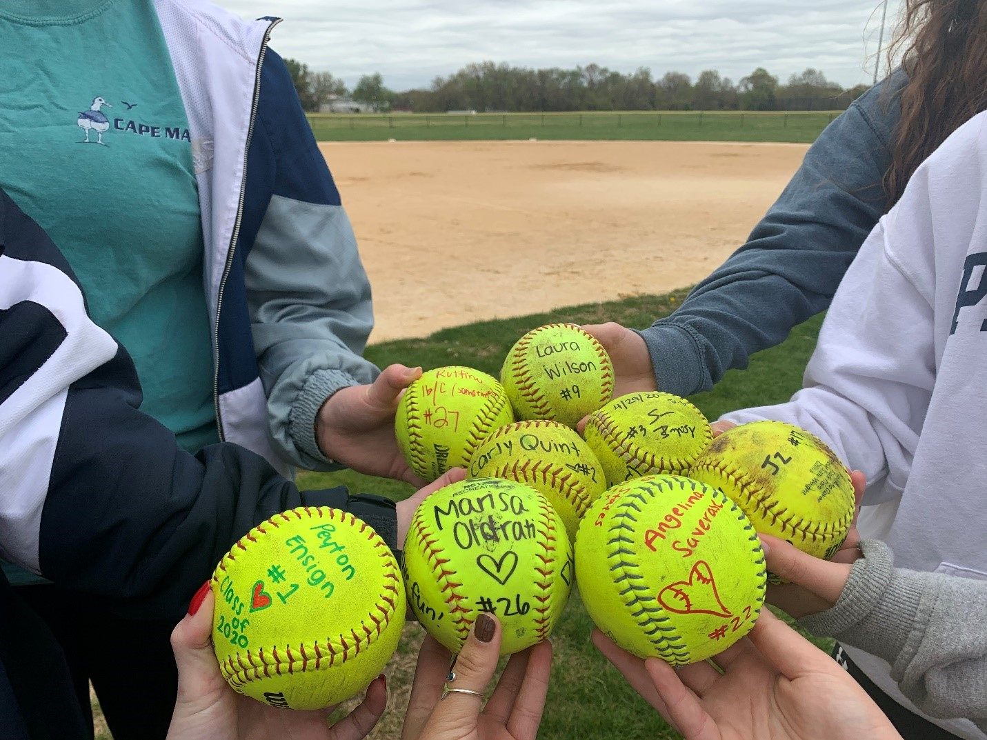 The team signs softballs commemorating their camaraderie.