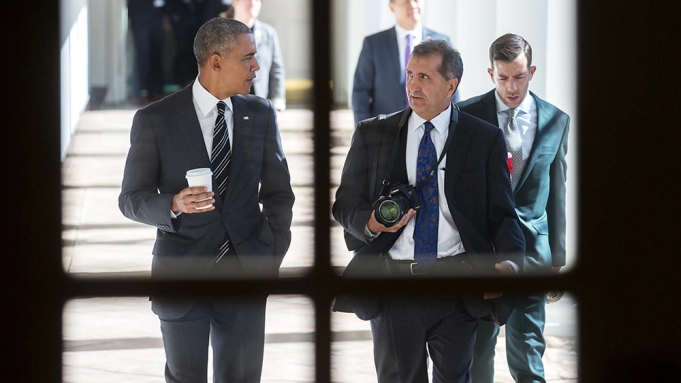 The subject of the documentary, Pete Souza, walks with former President Barack Obama.